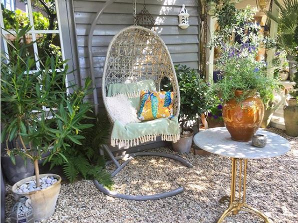 a wicker suspended chin hanging in a graevl garden surrounded by potted plants