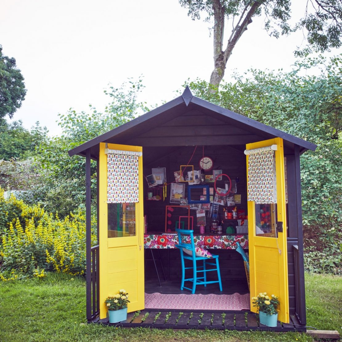 a wooden cabin with door painted bright yellow and an artistic collection of pictures and frames on the wall