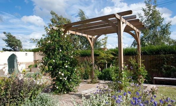 a wooden pergola with plants growing all around it