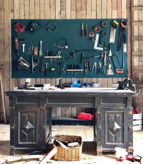 a worn antique desk used as a work bench, with an organised tool storage board on the wall behind