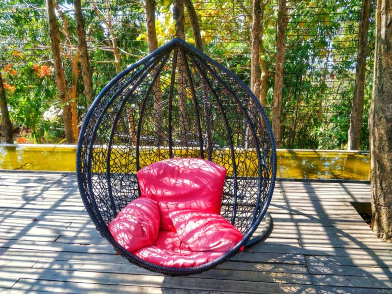 an ornate black swing chair with squashy red cushions on a deck