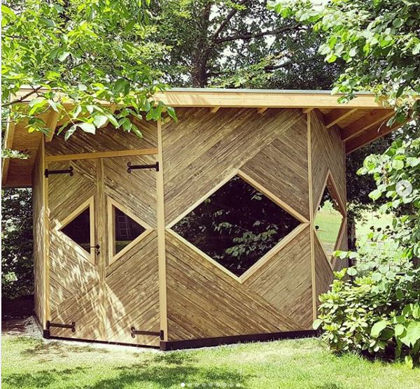 an octagonal garden cabin with diamond shaped windows, double doors and decorative wood panelling
