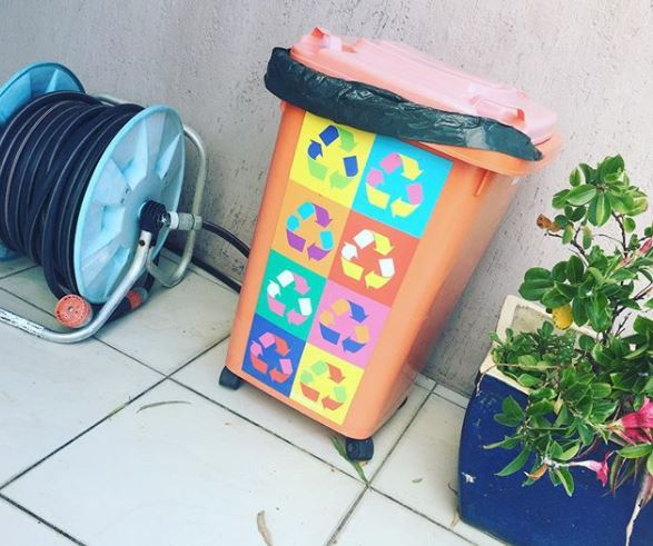 an orange wheelie bin with a decal of multicoloured recycling symbols