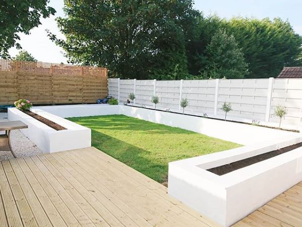 an organised garden with rectangluar lawn, wooden deck and long raised planters painted white