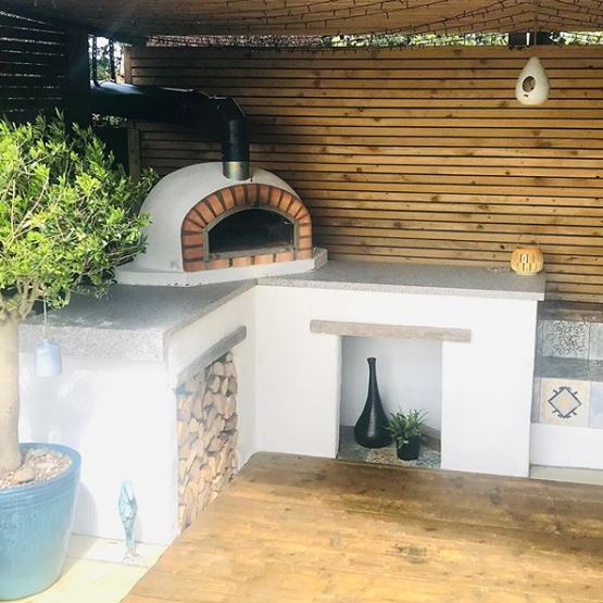 an outdoor kitchen area with a log stack and wood-fired pizza oven on a stone counter