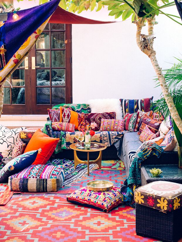 an outdoor seating area crammed with bright cushions and rugs in embroidered fabrics