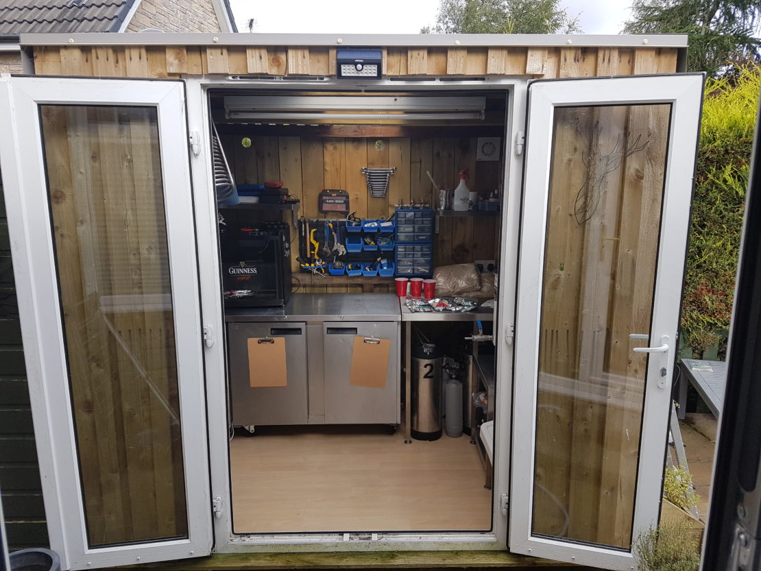 an outdoor shed filled with home-brewing equipment