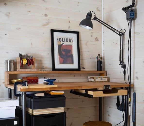 an outdoor workspace, with a small, neat desk area and anglepoise lamp