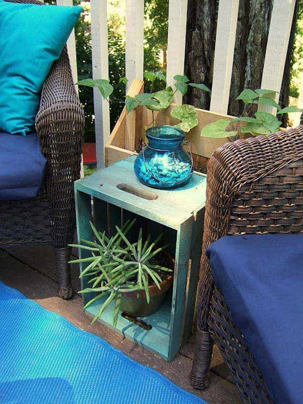 an upended crate, painted blue, being used as a side table for a plant and decorative blue vase, between two wicker chairs with blue cushions