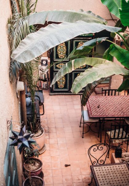 Moroccan themed garden ideas - a courtyard with tall leafy plants, a tiled dining table and painted cabinet