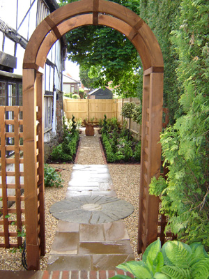 archway leading into a narrow garden with a path running all the way down the middle