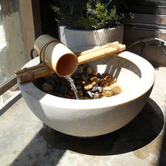 a small DIY bamboo water feature, with a trickle falling into a pebble-fulled bowl beneath