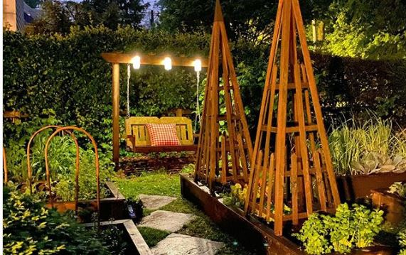 a rustic wooden swing bench with three bright overhead lights attached