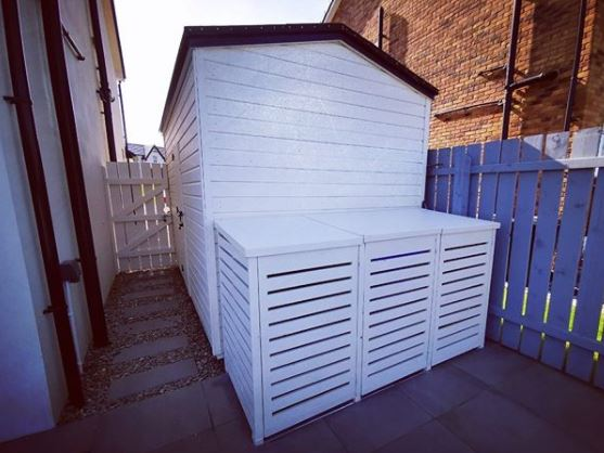 bin storage ideas next to a shed, painted the same colour to blend in