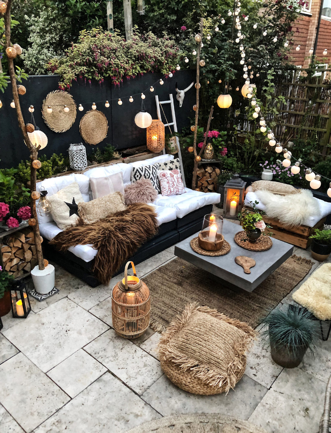 bohemian garden ideas - an eclectic seating area with assorted scatter cushions, string lights and candles