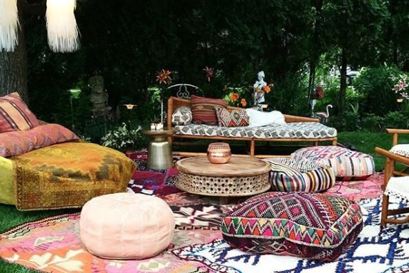 bohemian garden ideas - garden seating laid out on grass with patterend rugs and floor cushions