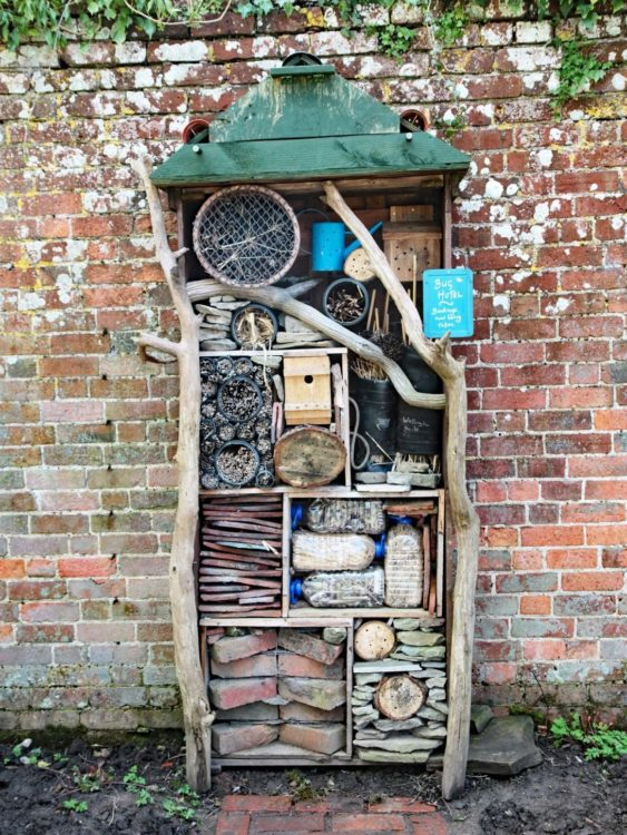 a tall, rustic insect hotel made from branches and garden debris