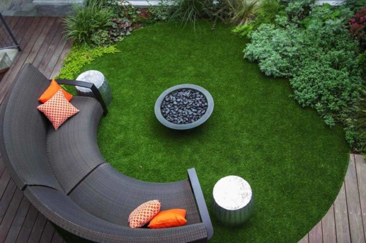 a circular lawn with a curved sofa and fire pit in the centre