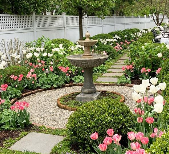 classical tiered water fountain in the centre of a gravel path surrounded by pretty flower beds