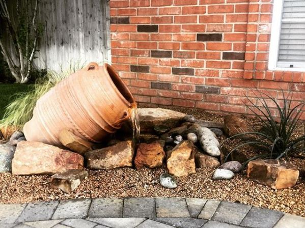 garden water feature ideas using a clay pot amphora fountain on its side, pouring into gravel