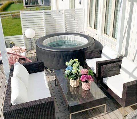 dark rattan garden furniture with white cushions next to an inflatable hot tub