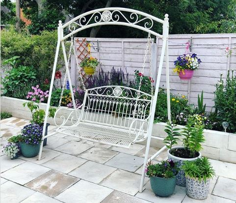 A white metal swing bench on a clean patio surrounded by flowers