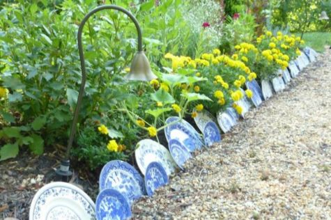 a flower bed edged with blue pattered ceramic plates in various sizes