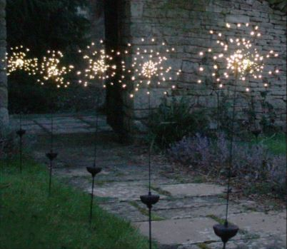 A row of solar powered garden lights that look like dandelions or sparklers