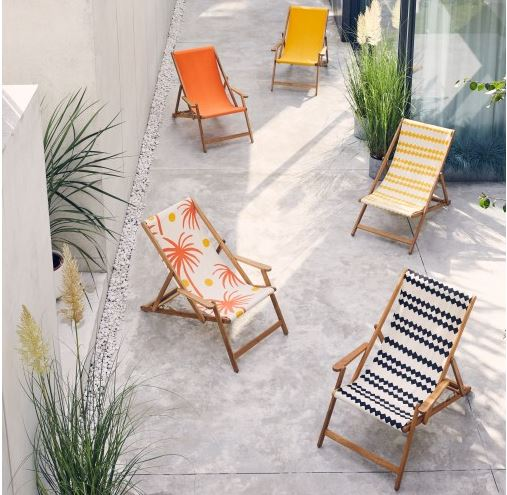 five brightly coloured deck chairs are staggered across a concrete patio