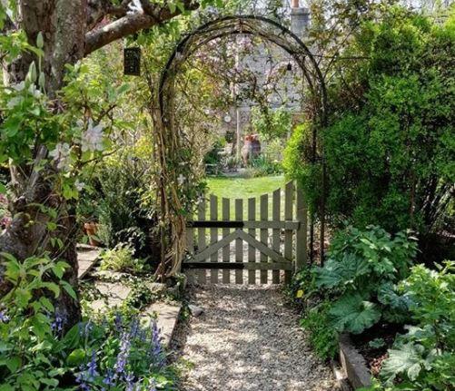 flowers grow over an archway across a pretty garden gate