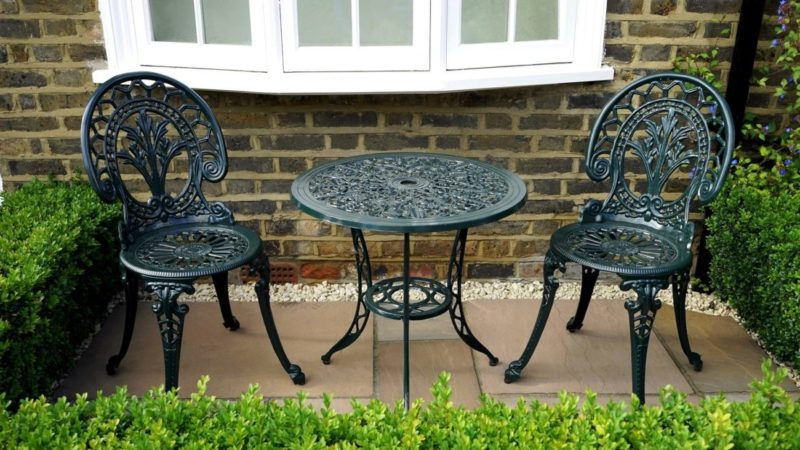 two intricate cast iron chairs either side of a matching table, on a small section of patio