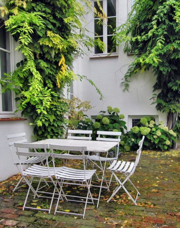 a white fold-up table with five fold-up chairs sitting in a leafy courtyard