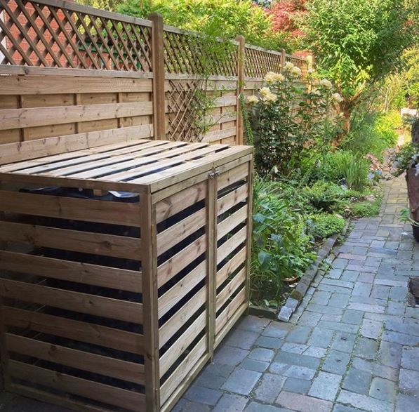 garden bin storage ideas - a bin store made from the same wood as the fence with double doors that bolt closed