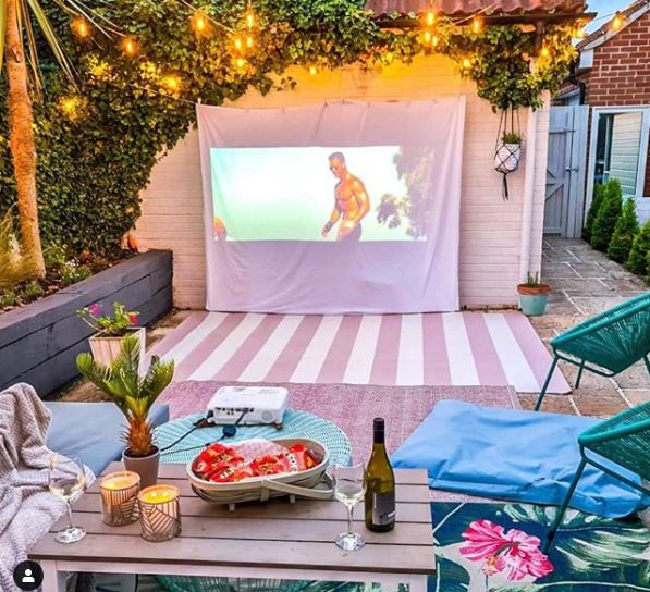 garden cinema screen made from a sheet on a shed, with a bowl of snacks and a bottle of wine
