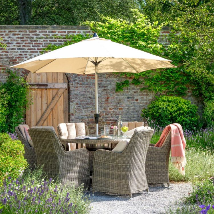 Timeless rattan chairs around a glass-topped table, under a parasol