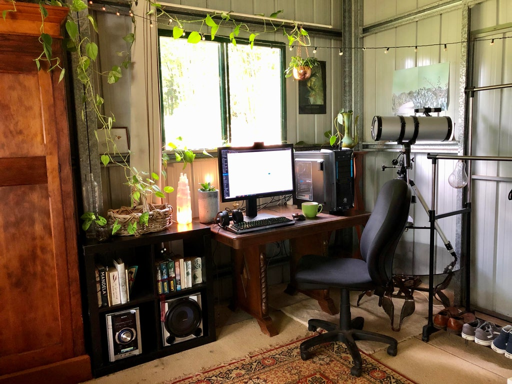 garden man cave ideas - a shed with desk, gaming PC, hi-fi system, telescope and other hobby paraphernalia