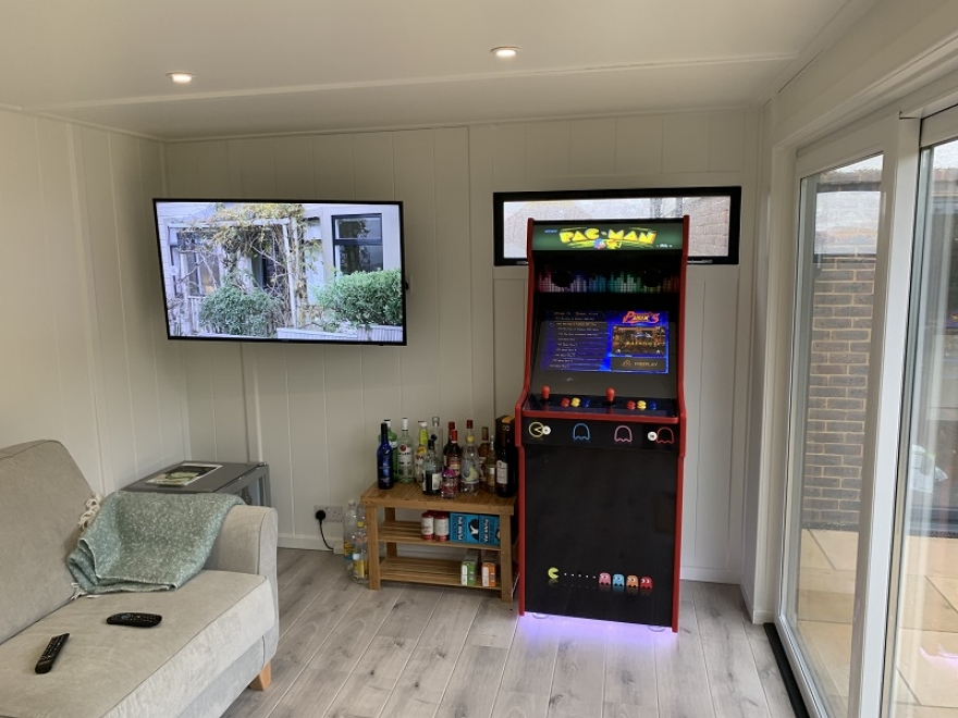 garden man cave with pacman arcade machine, sofa and shelves with a variety of alcohol bottles