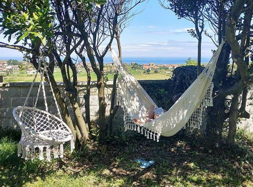A tasselled swing chair and matching hammock hang from trees and overlook the countryside
