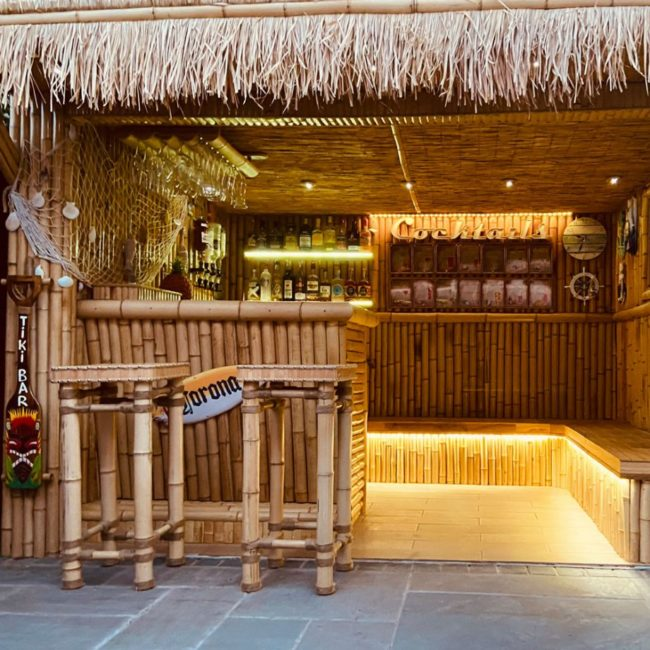 a tiki style garden bar made from bamboo with a grass roof