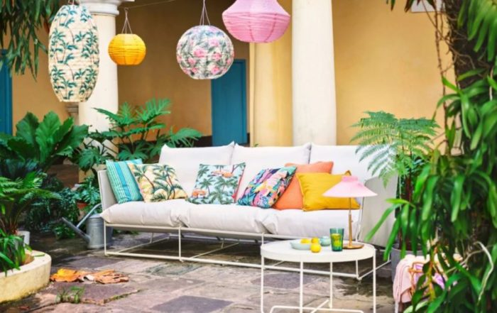 a tropical outdoor seating area with brightly patterned cushions and multi-coloured lanterns