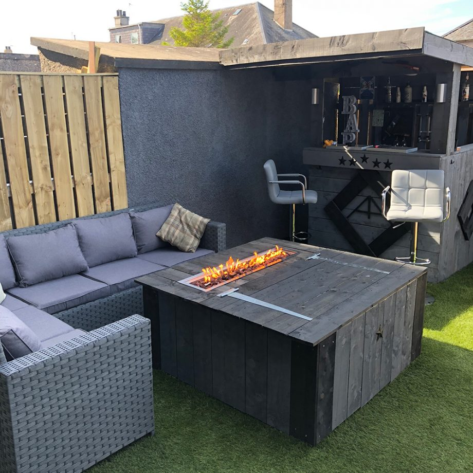 a stylish garden bar with corner sofa and fire pit coffee table