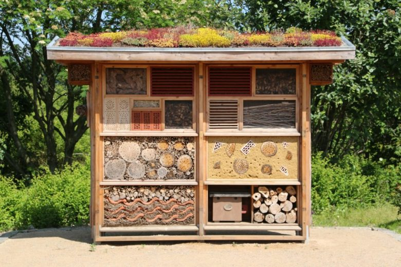 a large insect hotel with various compartments and a green roof