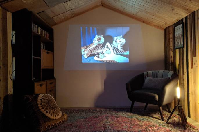 inside a garden man cave with a projector, playing an animated film