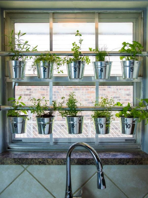 kitchen garden ideas - two rails across a kitch window with pots of herbs hanging from them