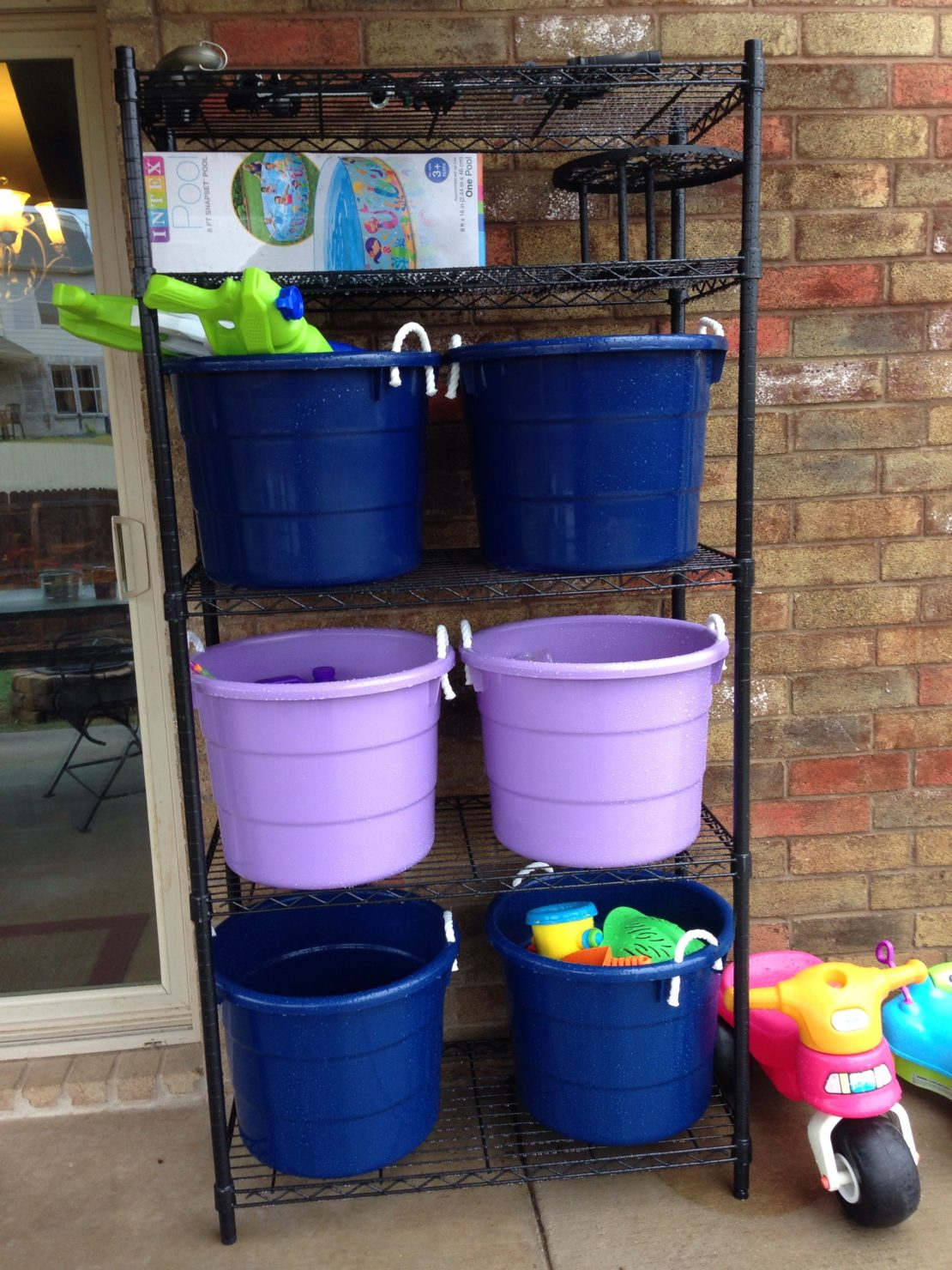 large plastic toy buckets on metal open shelving outside