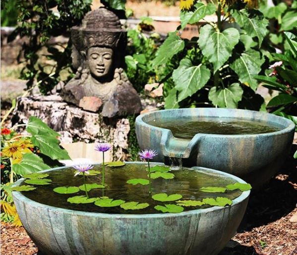 one large zen water bowl pouring into another, next to a small sculpture of buddha