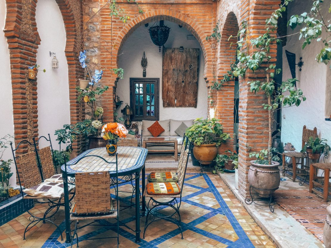 a busy courtyard with pretty brickwork, a tiled floor, dining table and potted plants
