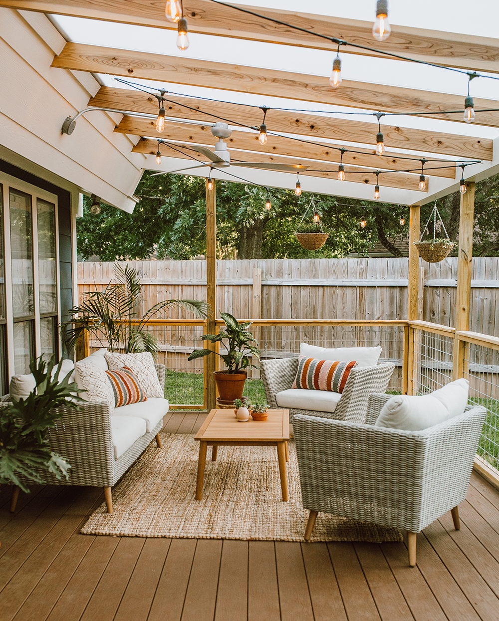 a simple deck with pale awning and string lighting going across it