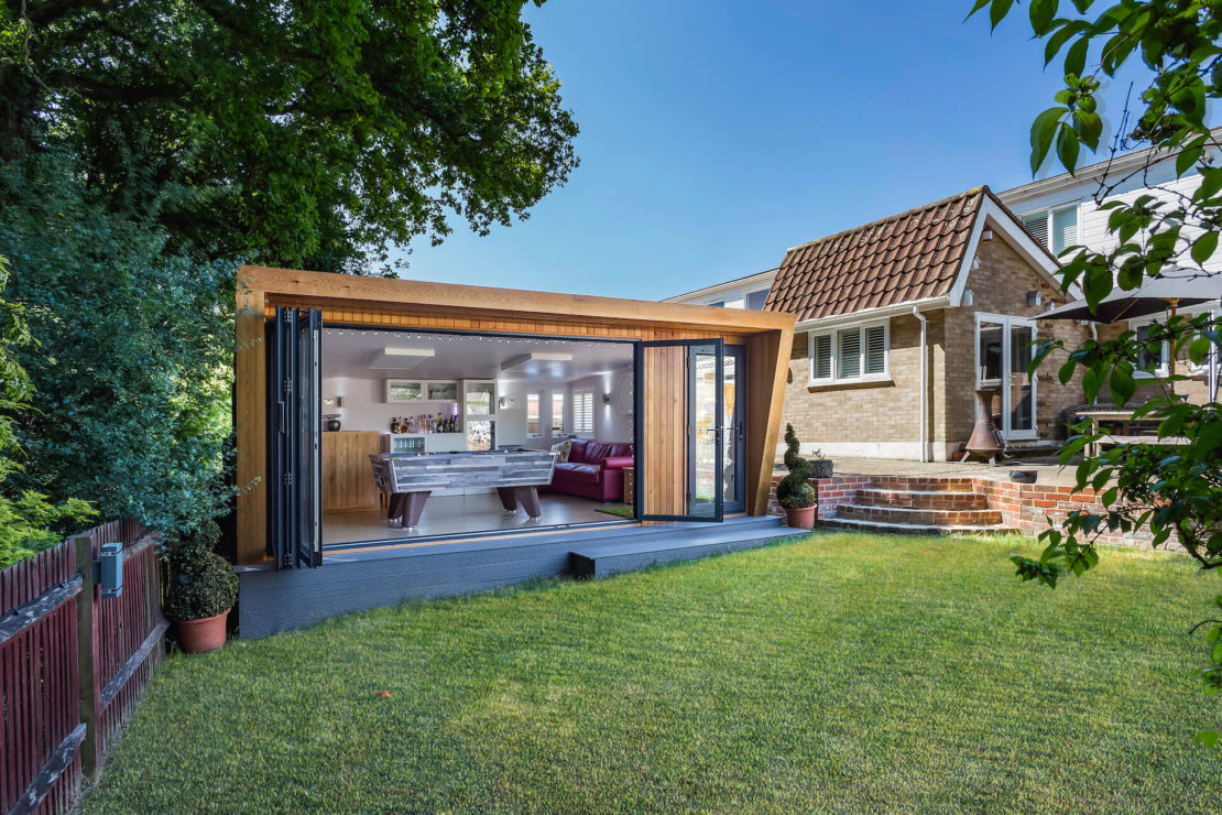 luxury garden man cave ideas - a modern shed with bifold doors, with a bar and foosball table inside