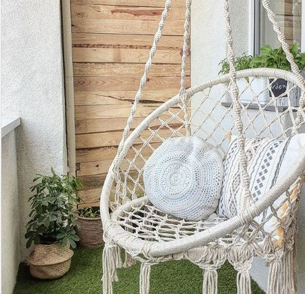 a macrame swing hanging on a small balcony